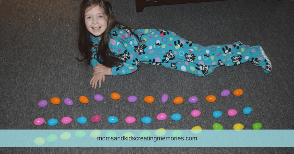 10 Fun Things to Do With Easter Eggs - My daughter laying next to patterns she made with Easter eggs