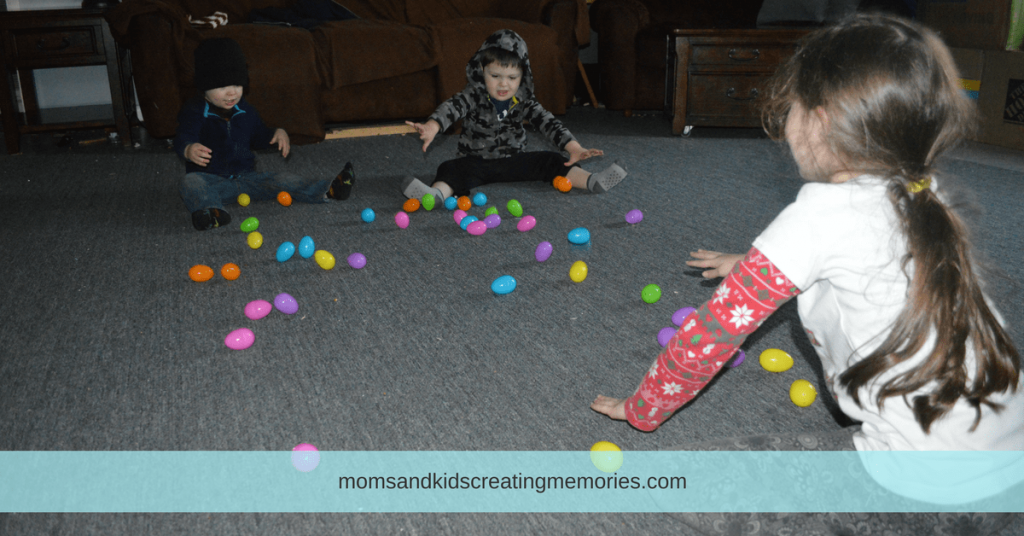 10 Fun Things to do with Easter Eggs - My three kids rolling Easter eggs back and forth to each other