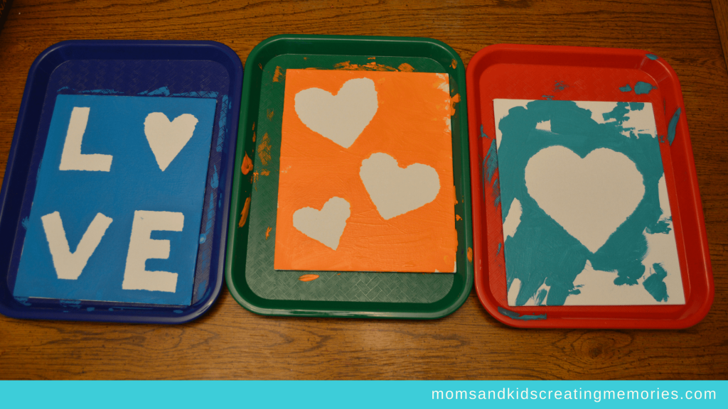 Canvas Art - the three canvases that the kids painted with the tape off and drying on their trays - hearts and Love