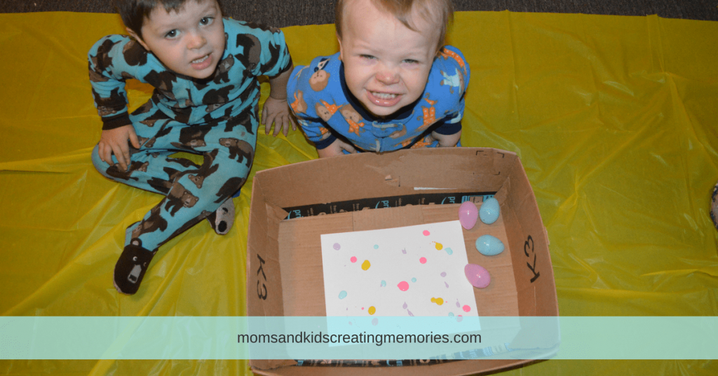 Easter Egg Painting - White Cardstock, with drops of paint on it, in a box with Easter eggs and my two boys ready to paint