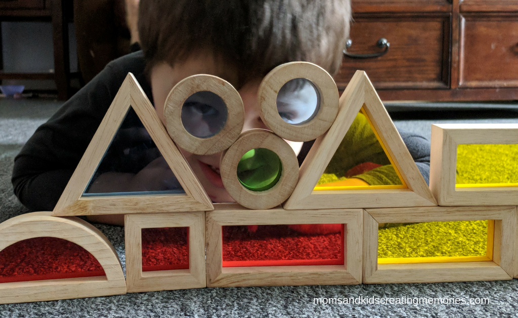 My son playing with blocks that have colored plastic in the middle of them. He loves these toys
