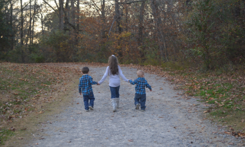 My three kids walking hand in hand down a path