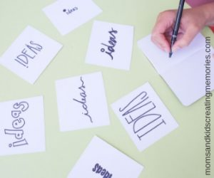 Table covered in cards that say ideas in different fonts and a person writing a note